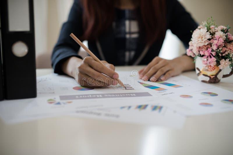 Biznesowa kobieta trzyma ołówek pracuje z wykresem na des zdjęcie royalty free