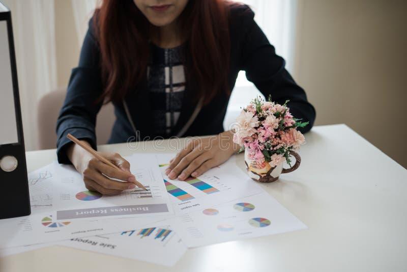 Biznesowa kobieta trzyma ołówek pracuje z wykresem na des zdjęcia stock