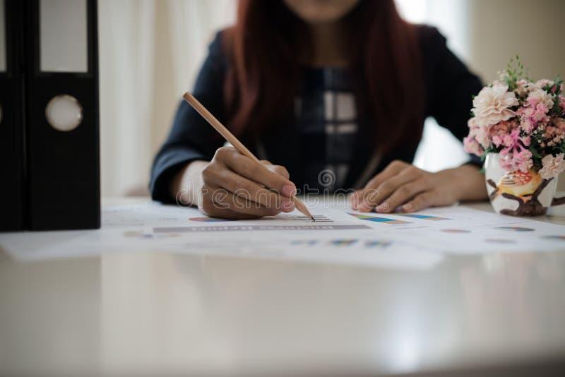 Biznesowa kobieta trzyma ołówek pracuje z wykresem na des obrazy stock