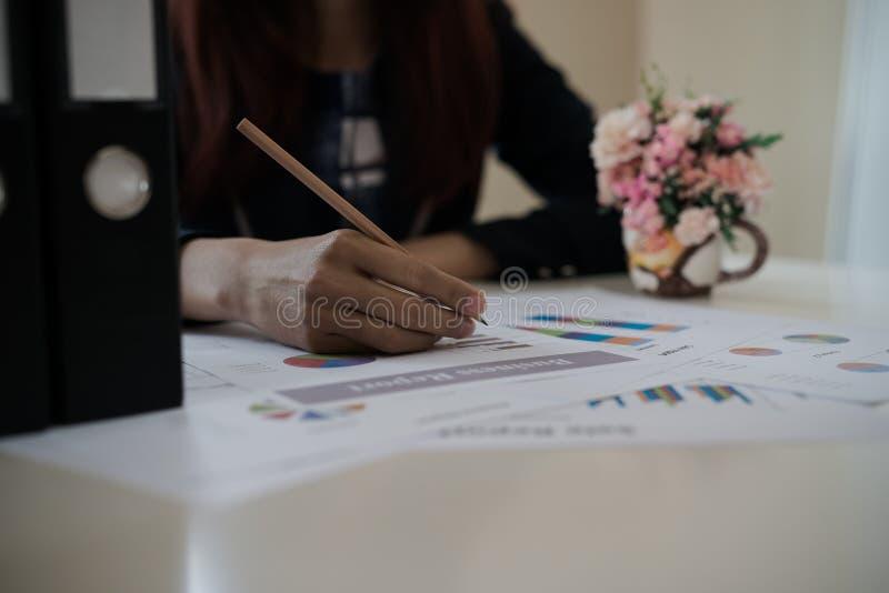 Biznesowa kobieta trzyma ołówek pracuje z wykresem na des zdjęcia royalty free