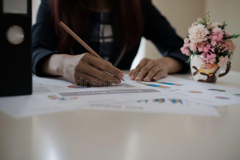 Biznesowa kobieta trzyma ołówek pracuje z wykresem na des fotografia royalty free