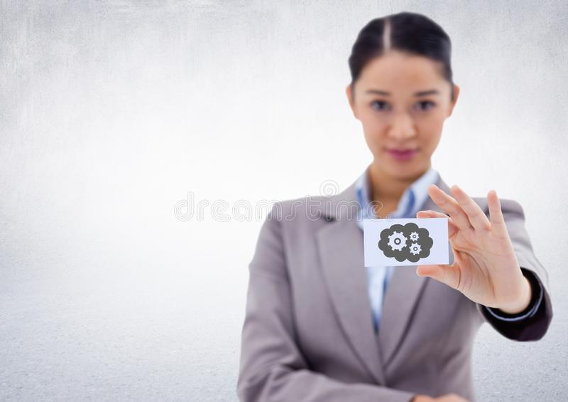 Biznesowa kobieta trzyma out karcianego seansu przekładni i chmury popielatą grafikę przeciw biel ścianie zdjęcia stock
