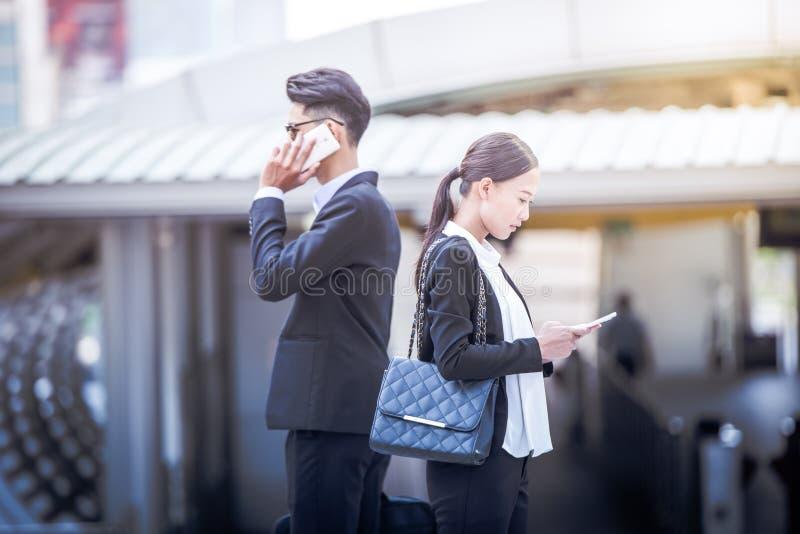 Biznesowa kobieta trzyma smartphone patrzeje puszek ekran w miasta i plamy biznesowym mężczyzna używa telefon technologię, komuni zdjęcie stock
