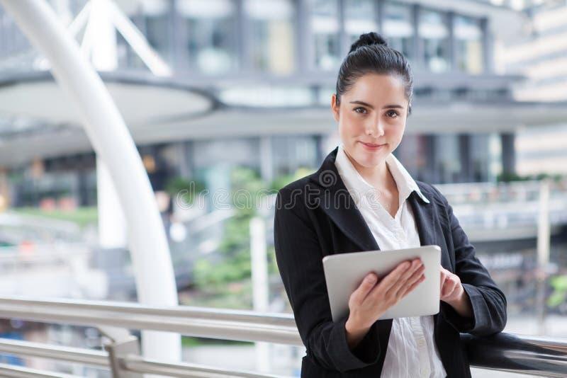 Biznesowa kobieta używa cyfrowego pastylka komputer na zewnątrz biura szczęśliwa młoda piękna dziewczyna pracuje na ogólnospołecz obrazy royalty free