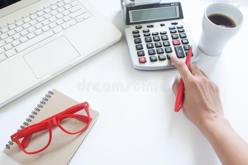 Biznesowa kobieta używa kalkulatora i laptopu na bielu zdjęcie royalty free