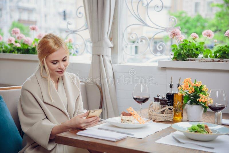Biznesowa kobieta używa mądrze telefon w restauraci zdjęcia royalty free