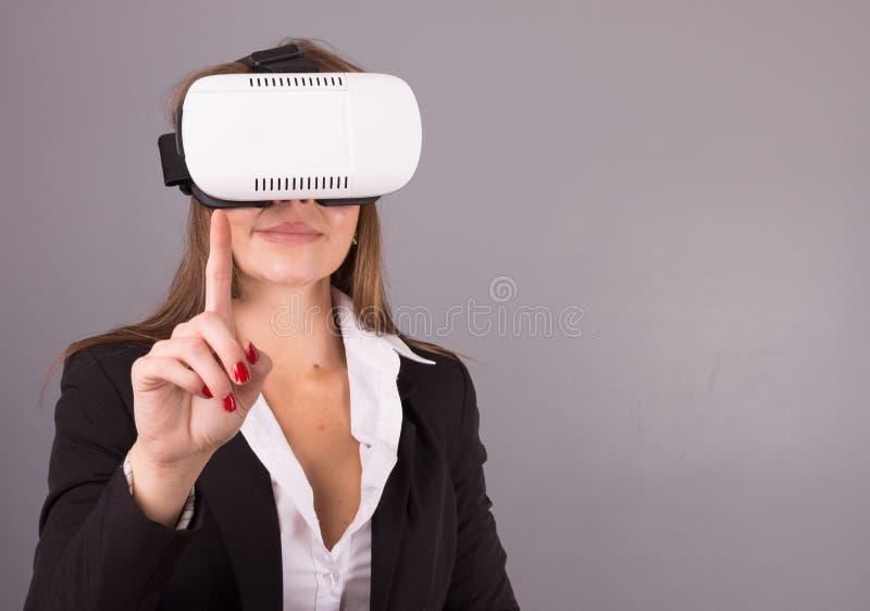 Biznesowa kobieta w noszonych technologii VR szkłach Ufna młoda kobieta w garniturze w rzeczywistości wirtualnej słuchawki zdjęcie royalty free