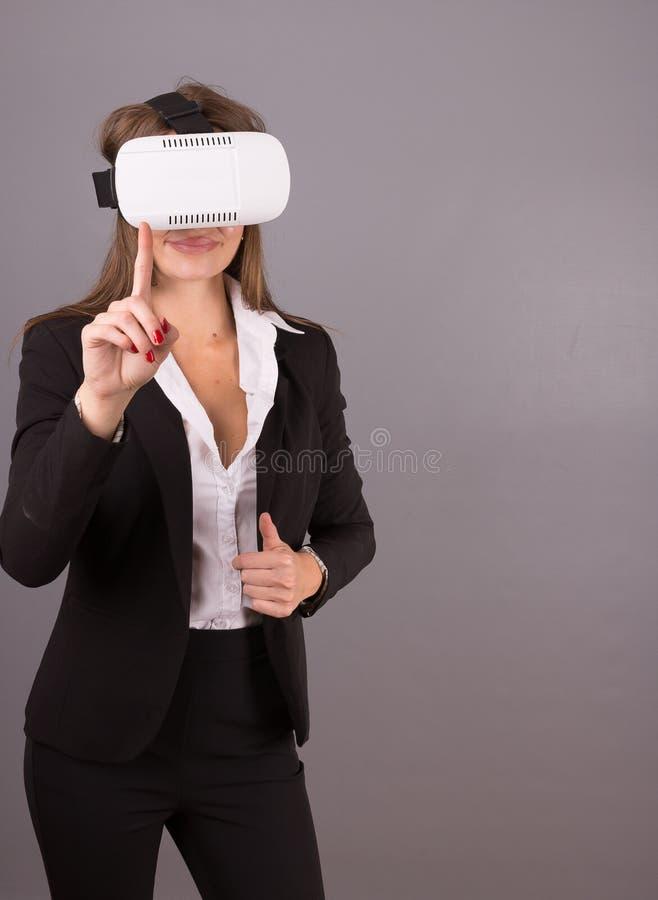 Biznesowa kobieta w noszonych technologii VR szkłach Ufna młoda kobieta w garniturze w rzeczywistości wirtualnej słuchawki fotografia royalty free