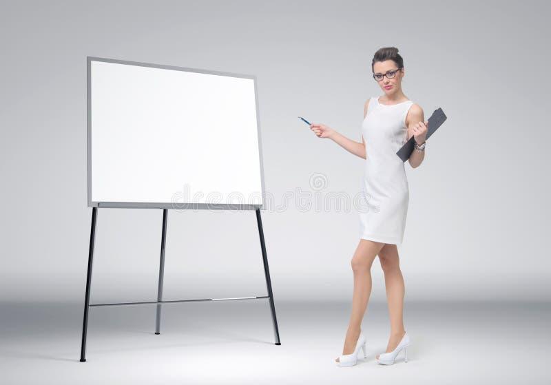 Biznesowa kobieta wyjaśnia przy deską zdjęcie royalty free