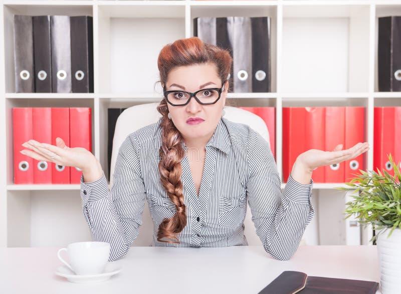 Biznesowa kobieta wzrusza ramionami ona ramiona w biurze zdjęcia stock