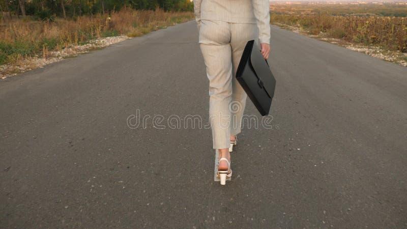 Biznesowa kobieta z czarną teczką chodzi w lekkim kostiumu i biel heeled buty chodzą wzdłuż asfaltu z obraz royalty free