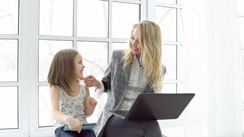Biznesowa kobieta z laptopem i małą dziewczynką z pastylki obsiadaniem dużym okno zdjęcia royalty free