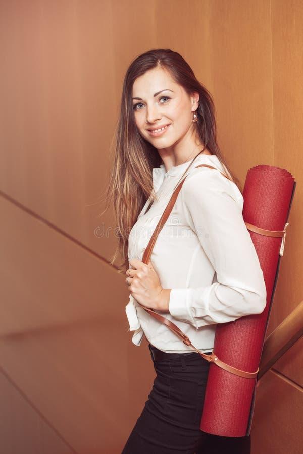 Biznesowa kobieta z niebieskimi oczami w białej bluzki koszula, czerni i dyszy mienia, przewożenia joga mata w biurze fotografia stock