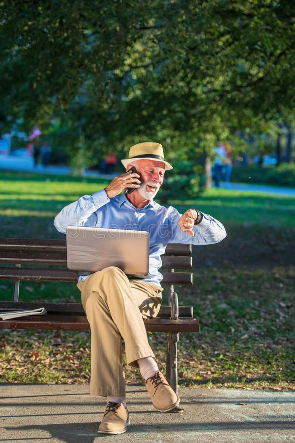 Biznesowa korespondencja Skupiający się dojrzały biznesmen używa laptop w parku podczas gdy siedzący fotografia stock