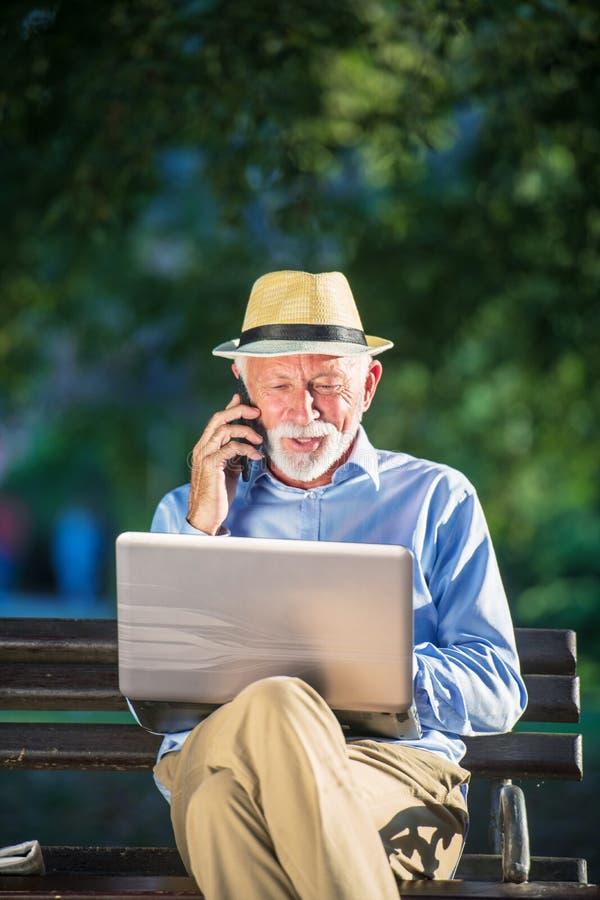 Biznesowa korespondencja Skupiający się dojrzały biznesmen używa laptop w parku podczas gdy siedzący obrazy stock