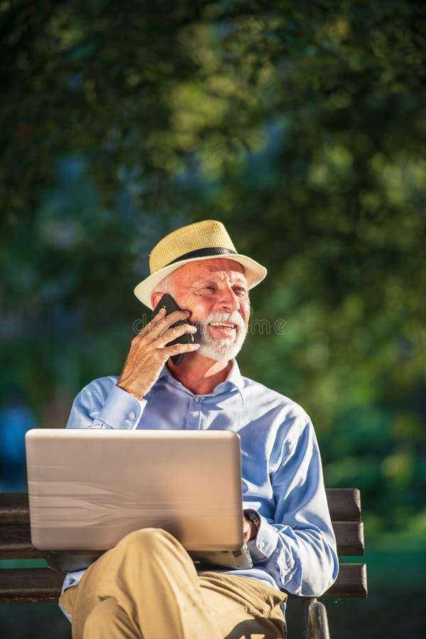 Biznesowa korespondencja Skupiający się dojrzały biznesmen używa laptop w parku podczas gdy siedzący zdjęcia stock