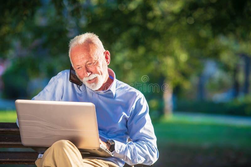 Biznesowa korespondencja Skupiający się dojrzały biznesmen używa laptop w parku podczas gdy siedzący zdjęcie stock
