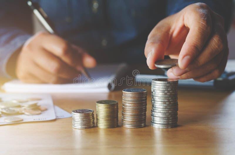 biznesowa księgowość z oszczędzanie pieniądze z ręki kładzenia monetami dalej obraz royalty free