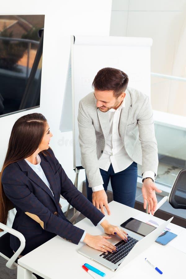 Biznesowa para pracuje wpólnie na projekcie przy nowożytnym biurem obraz royalty free