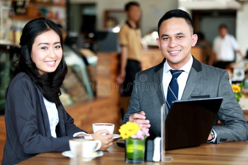 Biznesowa para uśmiechnięta i patrzeje kamerę podczas gdy spotykający zdjęcia stock