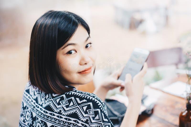 Biznesowe azjatykcie kobiety używają smartphone w rocznika cof podczas gdy siedzący fotografia royalty free