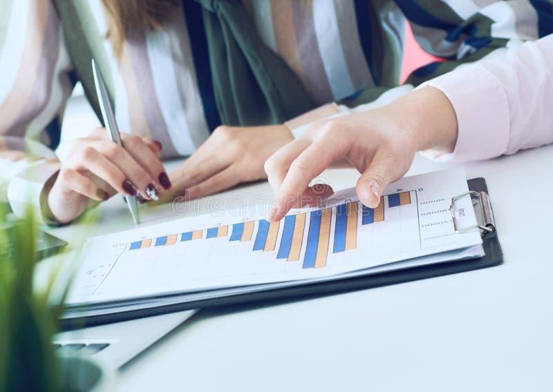 Biznesowe kobiety dyskutuje mapy pokazuje rezultaty ich pomyślna praca zespołowa wykresy i W?a?nie r?ki nad obrazy stock