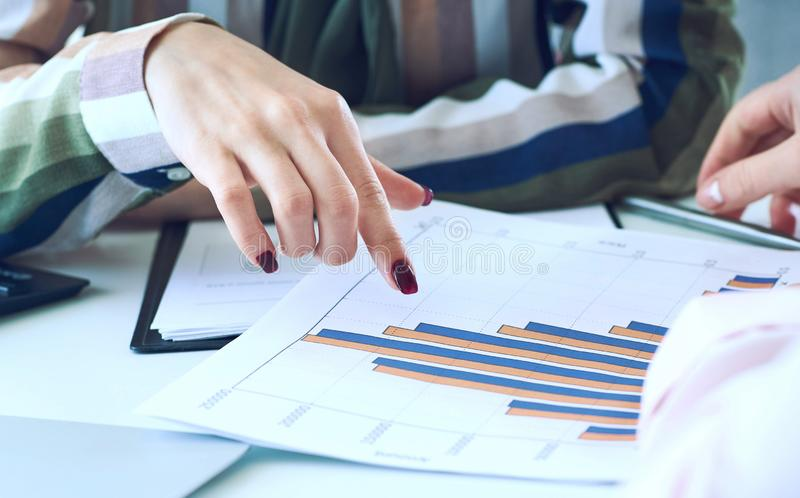 Biznesowe kobiety dyskutuje mapy pokazuje rezultaty ich pomyślna praca zespołowa wykresy i W?a?nie r?ki nad fotografia stock