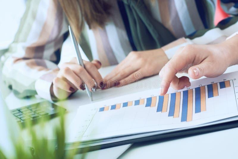 Biznesowe kobiety dyskutuje mapy pokazuje rezultaty ich pomyślna praca zespołowa wykresy i W?a?nie r?ki nad fotografia royalty free