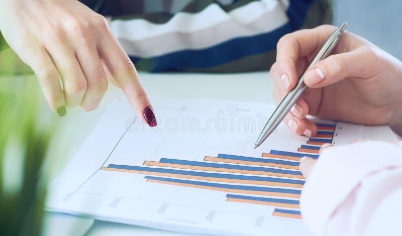 Biznesowe kobiety dyskutuje mapy pokazuje rezultaty ich pomyślna praca zespołowa wykresy i W?a?nie r?ki nad zdjęcie stock