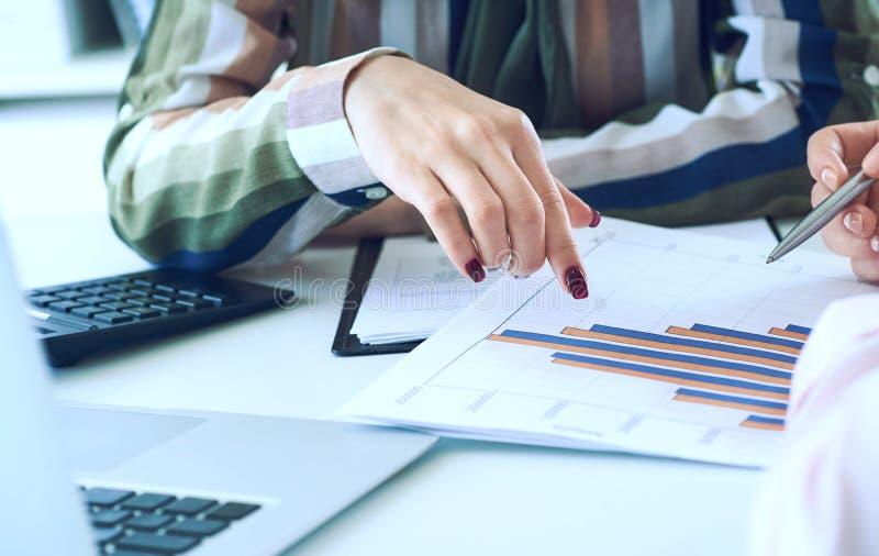 Biznesowe kobiety dyskutuje mapy pokazuje rezultaty ich pomy?lna praca zespo?owa wykresy i W?a?nie r?ki nad fotografia stock