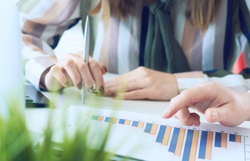 Biznesowe kobiety dyskutuje mapy pokazuje rezultaty ich pomy?lna praca zespo?owa wykresy i W?a?nie r?ki nad zdjęcie royalty free