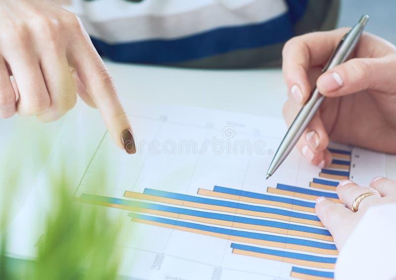 Biznesowe kobiety dyskutuje mapy pokazuje rezultaty ich pomy?lna praca zespo?owa wykresy i W?a?nie r?ki nad zdjęcia royalty free