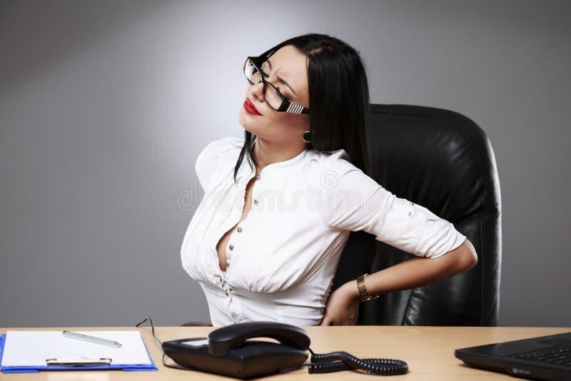 Biznesowe kobiety ma ból pleców przy biurem zdjęcie stock