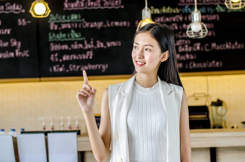 Biznesowe kobiety wskazuje mienie kawę Kobiety ono uśmiecha się szczęśliwy przy sklep z kawą obraz royalty free