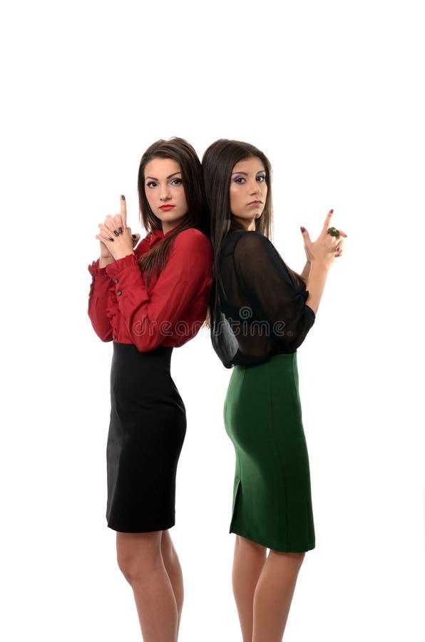 Biznesowe kobiety z powrotem popierać strzelaninę z imaginacyjnymi pistoletami, pracy zespołowej pojęcie obraz royalty free