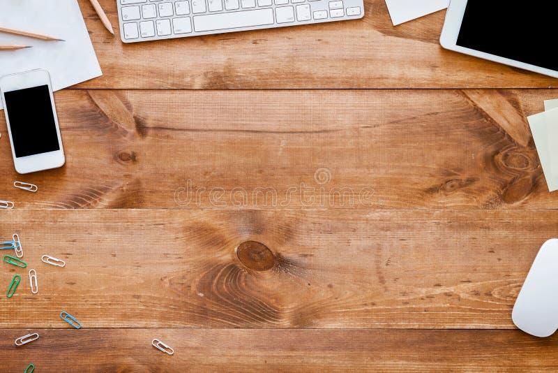 Biznesowe przyrząd dostawy na drewnianego biurka biurowym tle, odgórny widok fotografia royalty free
