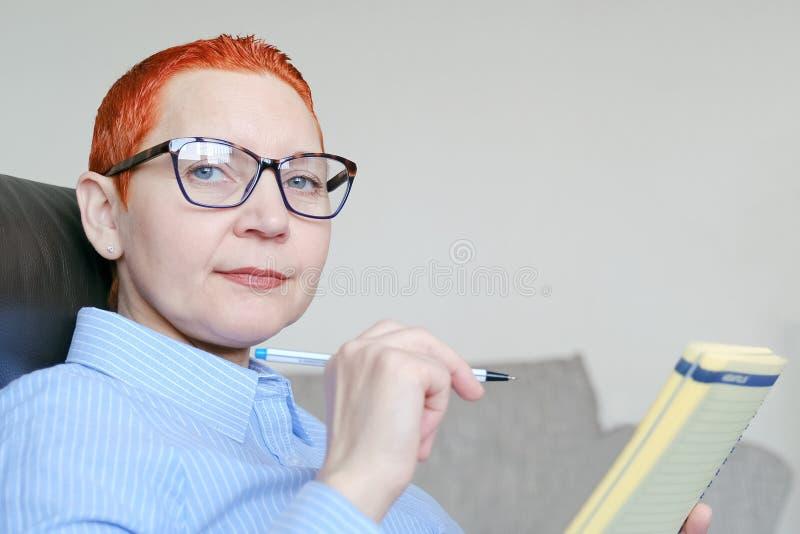 biznesowego krzesła siedząca kobieta Atrakcyjny młody bizneswomanu obsiadanie w krześle, patrzeje dokumenty obrazy stock