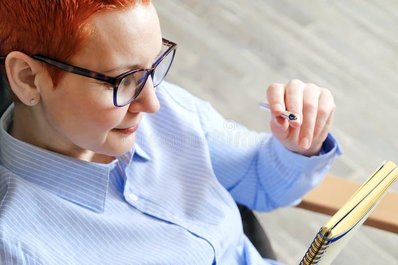 biznesowego krzesła siedząca kobieta Atrakcyjny młody bizneswomanu obsiadanie w krześle, patrzeje dokumenty zdjęcie stock