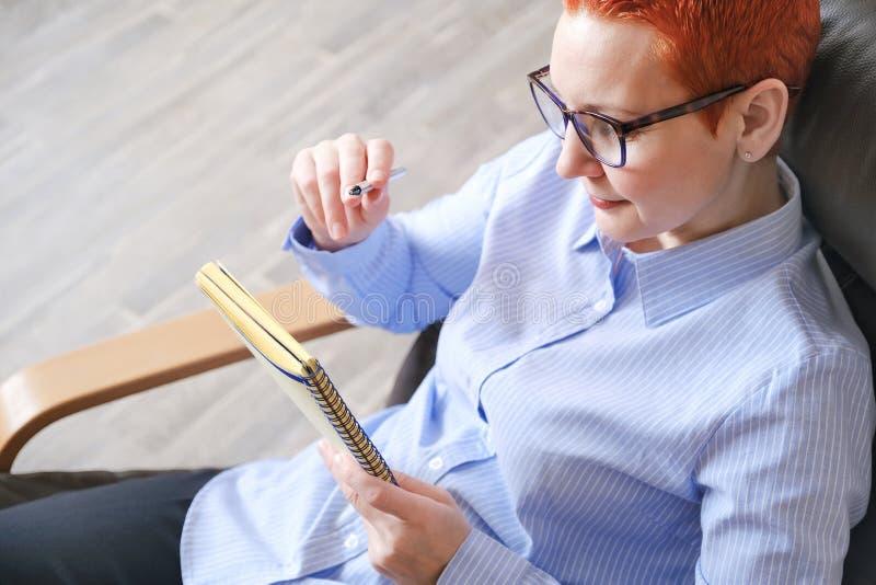 biznesowego krzesła siedząca kobieta Atrakcyjny młody bizneswomanu obsiadanie w krześle, patrzeje dokumenty obrazy royalty free