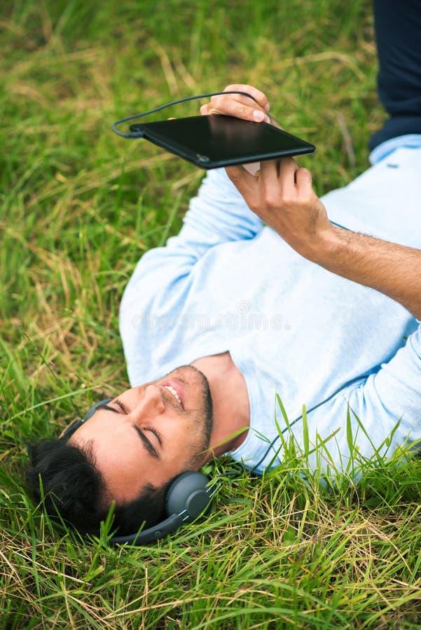 Biznesowego mężczyzny lying on the beach na zielonej trawie słucha muzykę, relaksuje z, przyrządem i hełmofonami obraz stock