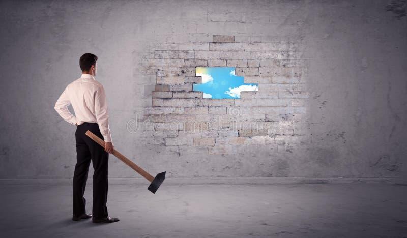 Biznesowego mężczyzna ciupnięcia ściana z cegieł z młotem obrazy stock