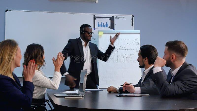 Biznesowego mężczyzna finishin mowa przed dużą widownią z tanem przy sala konferencyjną zdjęcie royalty free