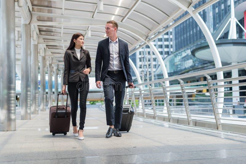 biznesowego mężczyzna i biznesowej kobiety odzieży czerni kostium chodzi wraz z bagażem na jawnej ulicie zdjęcie royalty free