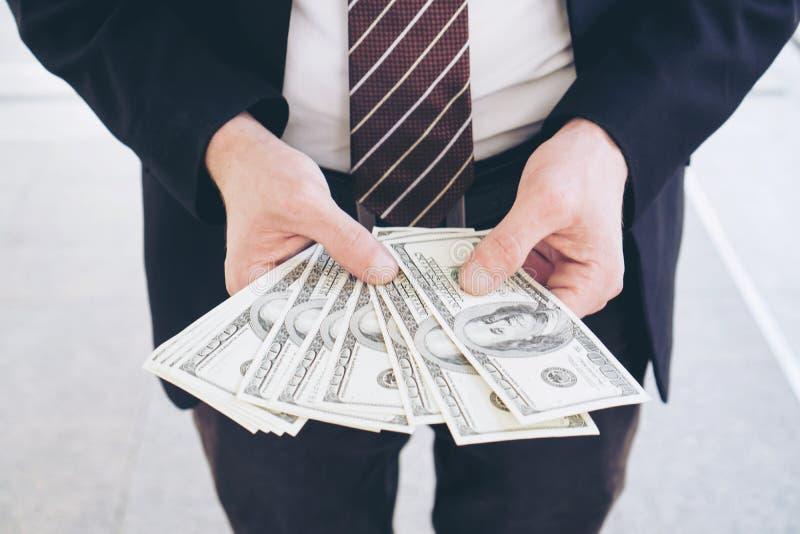 Biznesowego mężczyzna mienia pieniądze dolara amerykańskiego rachunki zdjęcia royalty free