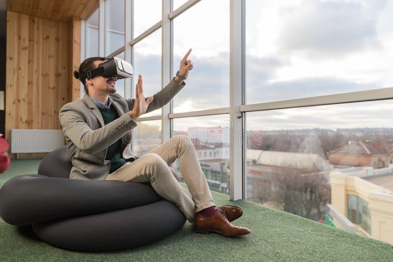Biznesowego mężczyzna odzieży Cyfrowego szkieł chwyta ręki rzeczywistość wirtualna Siedzi w frontowym Panoramicznym Nadokiennym b obraz stock