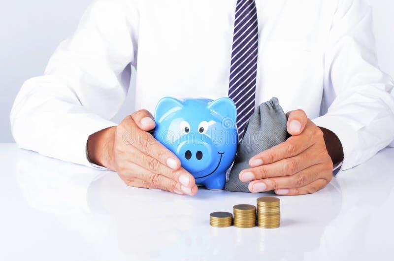 Biznesowego mężczyzna ręka trzyma błękitnego prosiątko banka i pieniądze zdojesteśmy z coi zdjęcie stock