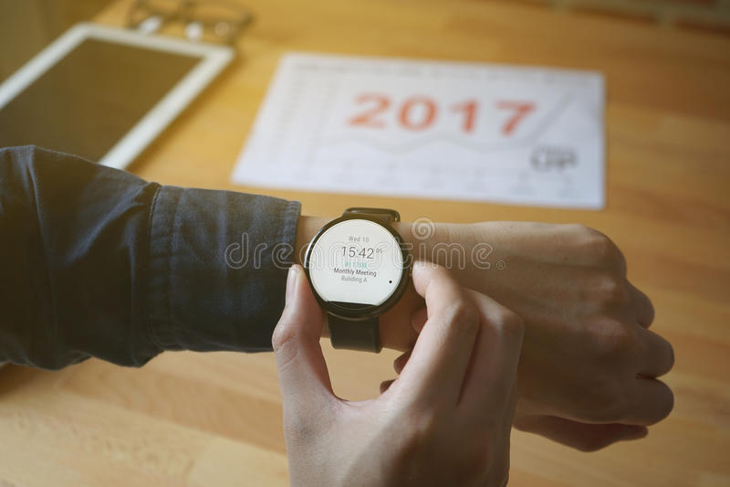 Biznesowego mężczyzna spojrzenia smartwatch dla sprawdzać czas spotykać przy sklep z kawą obraz stock