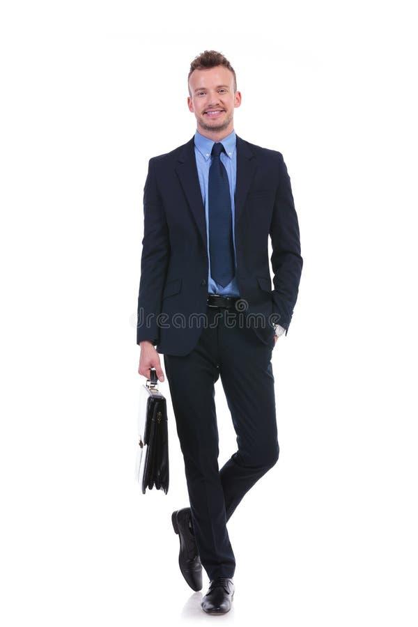 Biznesowego mężczyzna stojaki z walizką i ręką w kieszeni zdjęcie royalty free