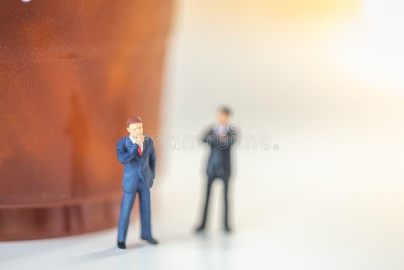 Biznesowego planowania poj?cie Zakończenie w górę Dwa biznesmenów minaiture postaci pozycji i główkowanie z plastikową filiżanką  obraz royalty free