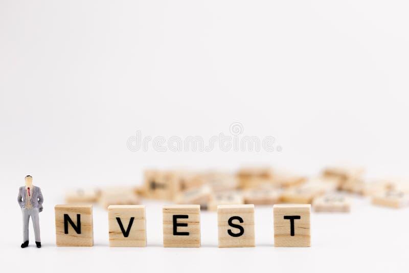 Biznesowej inwestyci pojęcie Miniaturowi ludzie małej postać biznesmena pozyci najpierw w drewnianym sześcianie z słowem inwestuj zdjęcia stock